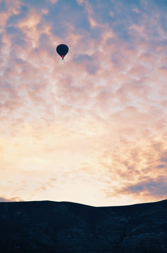 Hot air balloon cruising up in the sky during sunrise